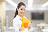 オフィスでファイルを手に微笑むビジネス女性