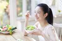 サラダを食べる笑顔の女性