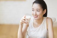 牛乳を手に微笑む女性