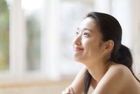 窓辺で上を見上げる笑顔の女性