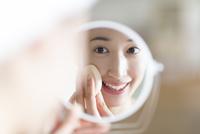 鏡の前でスキンケアをする微笑む女性