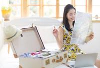 旅行の準備をする笑顔の女性 33000001868| 写真素材・ストックフォト・画像・イラスト素材|アマナイメージズ
