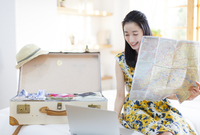 旅行の準備をする微笑む女性 33000001876| 写真素材・ストックフォト・画像・イラスト素材|アマナイメージズ