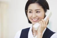 電話をする制服姿の女性 33000001927| 写真素材・ストックフォト・画像・イラスト素材|アマナイメージズ