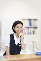 電話をする制服姿の女性