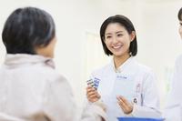 薬の説明をする女性薬剤師と患者