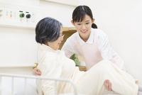 患者をベッドから起こす女性看護師 33000002010| 写真素材・ストックフォト・画像・イラスト素材|アマナイメージズ