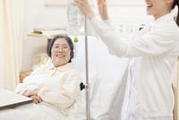 点滴を準備する女性看護婦と話をする患者