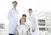 屋上で車椅子の患者に添う医師と看護師と女の子