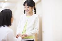 女の子の手に手添える女性医師