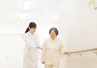 患者の歩行の手助けをする女性看護師