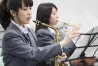 音楽室で楽譜をめくる女子学生 33000002270| 写真素材・ストックフォト・画像・イラスト素材|アマナイメージズ