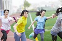 陸上競技場でバトンの手渡しをする女子学生たち