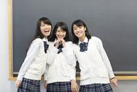 黒板の前に笑顔で並ぶ女子高校生たちのポートレート