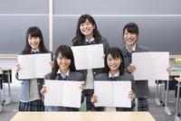教室でノート開いて笑う女子高校生たちのポートレート