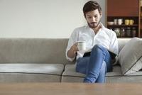 ソファーに座りカップを手に持って本を読む男性