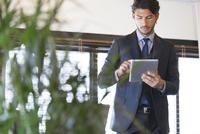 オフィスでタブレットPCを見るビジネス男性