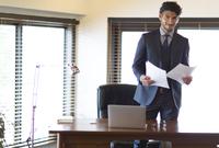 オフィスで資料を持ち微笑むビジネス男性