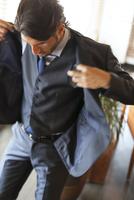 オフィスでスーツのジャケットを羽織るビジネス男性
