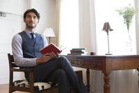 ソファーに座り本を持って微笑むビジネス男性