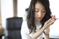 オフィスのデスクで前かがみで考え込むビジネス女性 33000002578| 写真素材・ストックフォト・画像・イラスト素材|アマナイメージズ