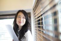オフィスの窓際で微笑むビジネス女性