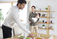 ダイニングで食事の準備をする男性と赤ちゃんを抱えて微笑む女性