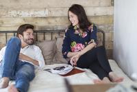 ベッドの上で談笑する男性と女性