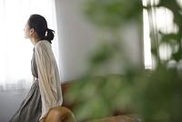 窓際のソファーに寄りかかって遠くを眺める女性の後ろ姿