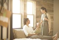 ベッドの上にいる男性にカップを手渡す女性