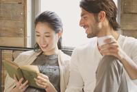 ベッドの上で本を読みながら笑い合う男性と女性