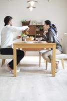 椅子に座ってサラダを取り分ける男性と微笑む女性