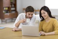 椅子に座ってパソコンを見る男性と女性