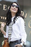 ウィンドウの前でサングラスをかけて微笑む女性
