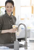 キッチンでコップを拭く女性
