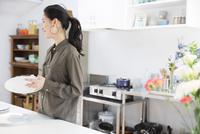 キッチンで食器を拭く女性