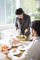 ダイニングテーブルでサラダを取り分ける女性と椅子に座る男性