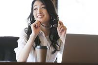 オフィスのデスクでくつろぐビジネス女性 33000002853| 写真素材・ストックフォト・画像・イラスト素材|アマナイメージズ