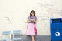 壁に寄り掛かってスマートフォンを操作する女性