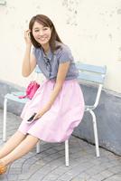 ベンチに座って微笑む女性 33000002890| 写真素材・ストックフォト・画像・イラスト素材|アマナイメージズ