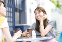 街中でカップを持って会話を楽しむ2人の女性