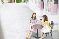 街中でカップを持って会話を楽しむ2人の女性 33000002908| 写真素材・ストックフォト・画像・イラスト素材|アマナイメージズ