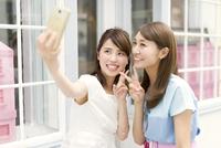スマートフォンで写真を撮る2人の女性