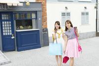カップを持ってショッピングを楽しむ2人の女性
