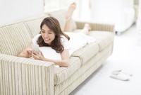 ソファの上でスマートフォンを見る女性