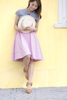 壁に寄り掛かって帽子を持って笑う女性 33000003036| 写真素材・ストックフォト・画像・イラスト素材|アマナイメージズ