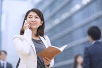 スマートフォンで通話するビジネス女性 33000003049| 写真素材・ストックフォト・画像・イラスト素材|アマナイメージズ