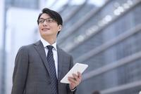 ビルを背景に立つビジネス男性 33000003050| 写真素材・ストックフォト・画像・イラスト素材|アマナイメージズ