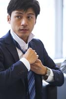 ネクタイを結ぶビジネス男性