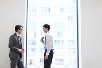 窓際で向かい合って会話をするビジネス男性